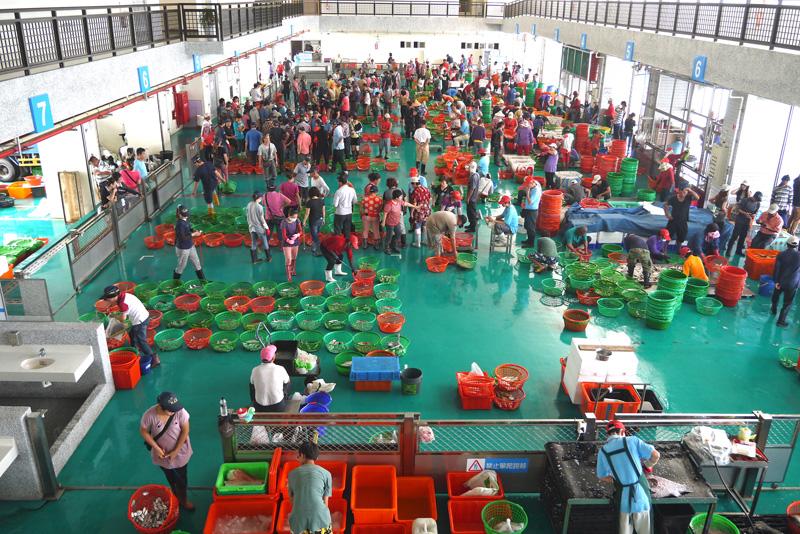 自梓官魚市場大樓二樓俯瞰而下,可一覽「喊魚仔」魚貨拍賣的獨特奇景。(圖∕李昀諭 攝)