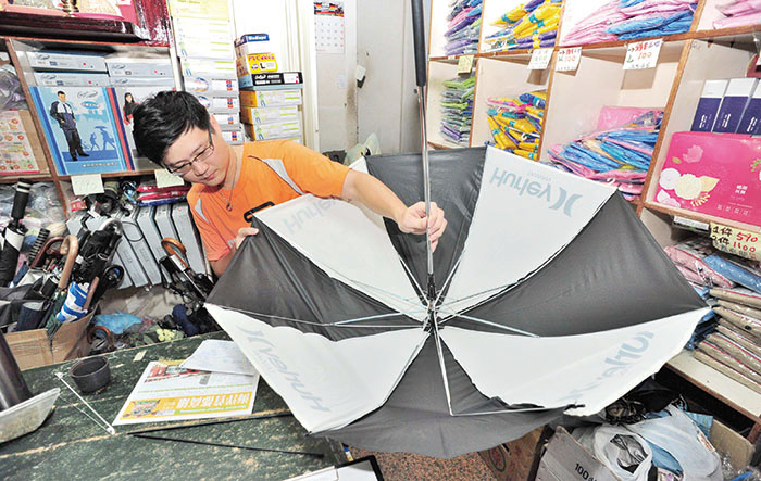 檢視傘況 Examining a broken umbrella